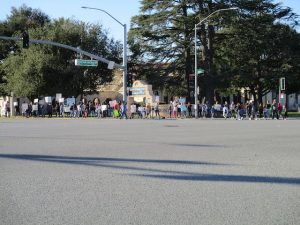 A group of parents and their children protest schools staying closed in front of Fremont High School